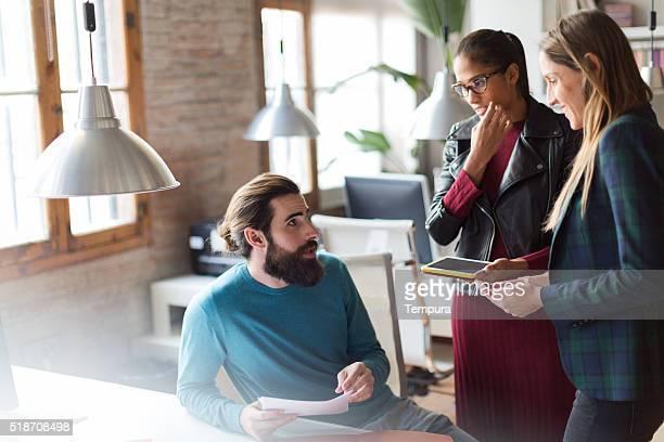 Reunião de negócios pequenos, três colegas de trabalho a olhar para um computador.