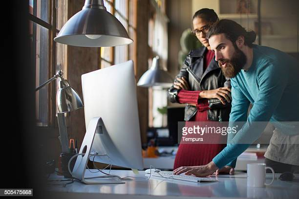 Business small meeting, two co-workers looking at computer.