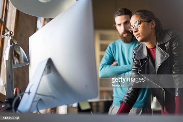 Reunião de negócios pequenos, dois colegas olhando para o computador.