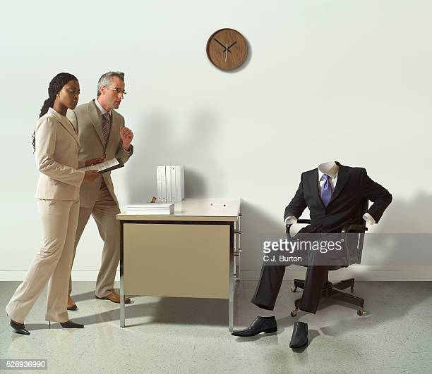 Business suit sitting on chair in office while surprise office workers looking at it