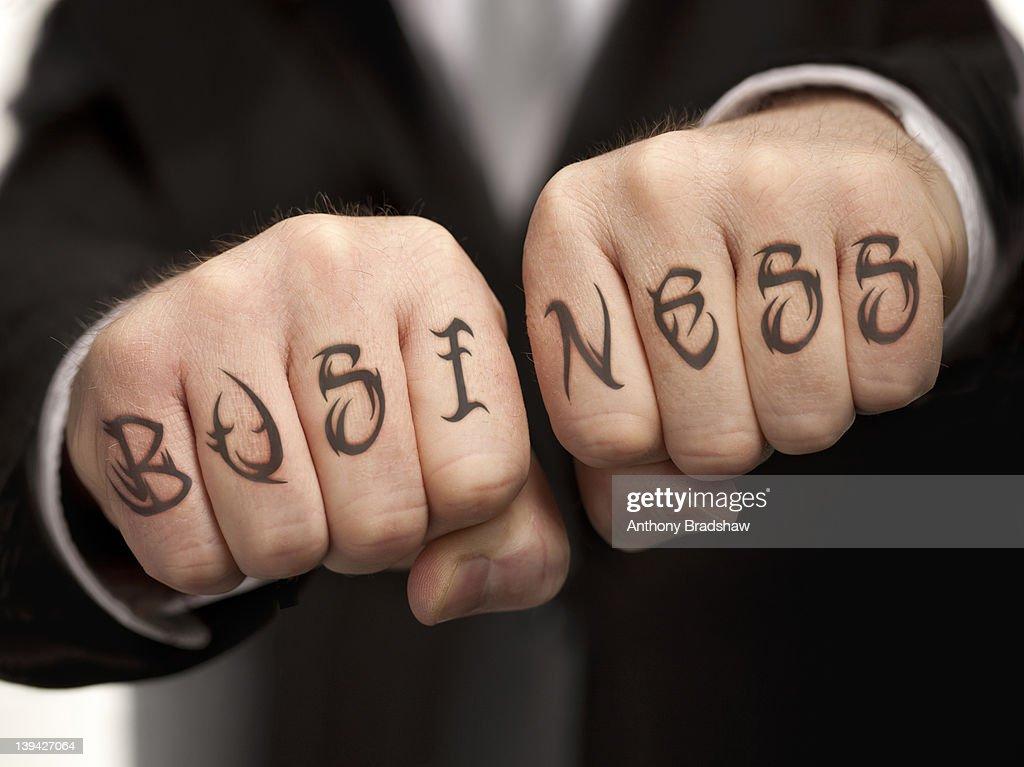 Business tattood on fists : Stock Photo