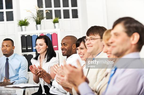 Business team applauding at conference table