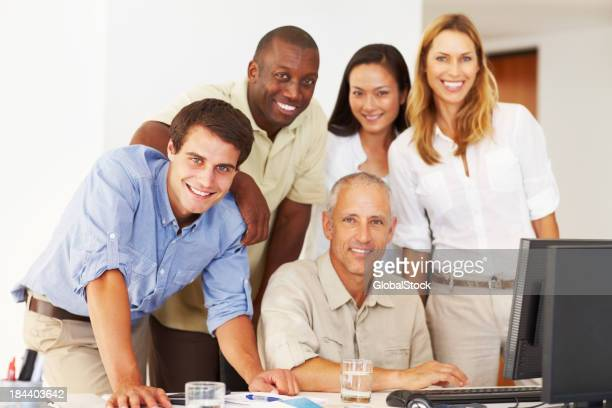 Business team around a computer, smiling and working