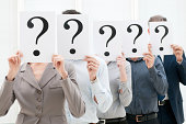 Group of business people hiding their faces behind a question mark sign at office.