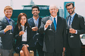 Group of five smiling business people standing on rooftop of office building, holding glasses with champagne and celebrating business success. Business team concept