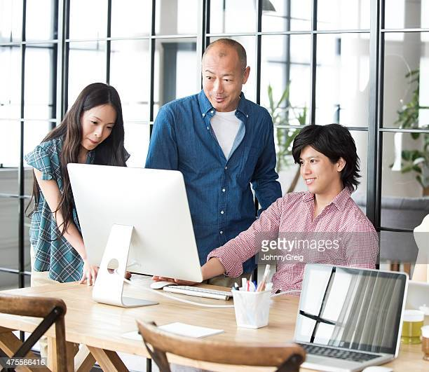 Business team discuss at computer