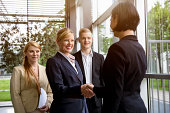 Business team greeting young female colleague