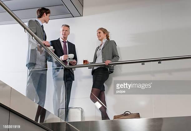 Équipe d'affaires ayant pause-café dans le couloir