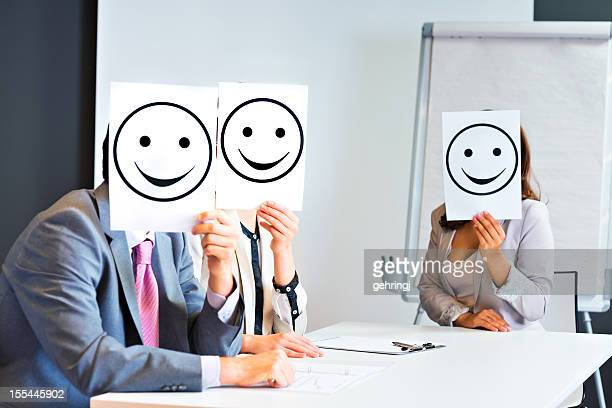 Business team holding happy smile sign
