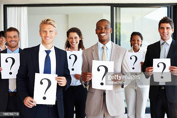 Business team holding question mark signs