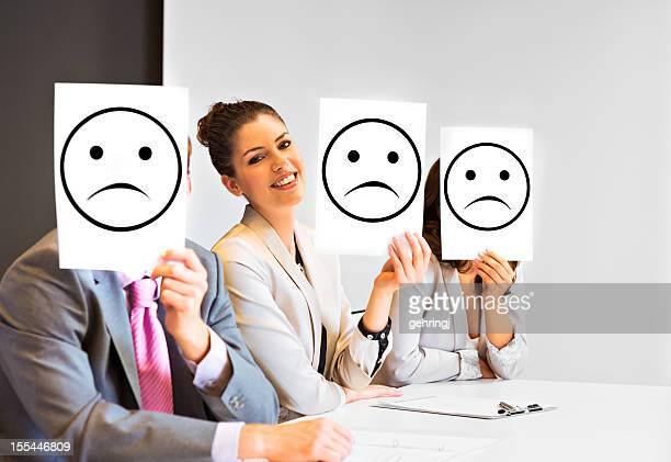 Business team holding sad signs