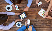 Top View of Arms of Group Young Business People Discussing Data on Electronic Gadgets Related to Social Media Marketing Impact
