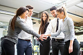 Business team joining hands together in the office.