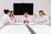 Photo of a business team meeting with a frustrated team member or manager.