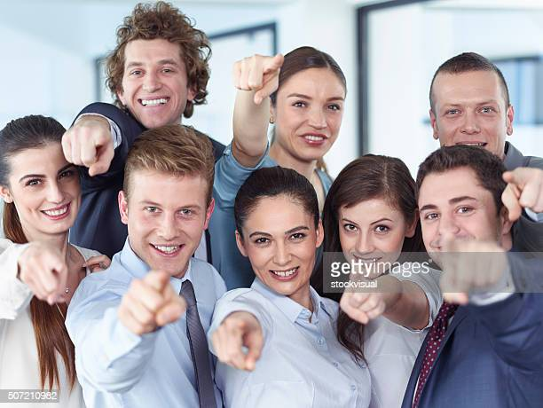 Business team pointing camera