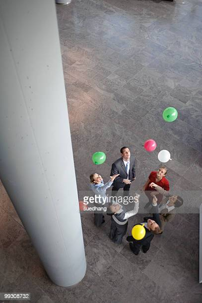Business team sets colored balloons free