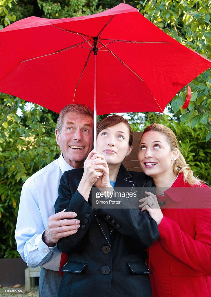 Business team shelter from rain : Stock Photo