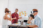 Young men and women sitting at a table with virtual reality goggles. Business team testing virtual reality headset in office meeting.