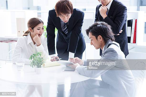 Business team that is meeting while looking at  tablet