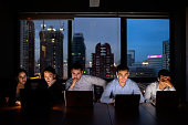 business team, three man and two woman working with computer overtime at night and low light