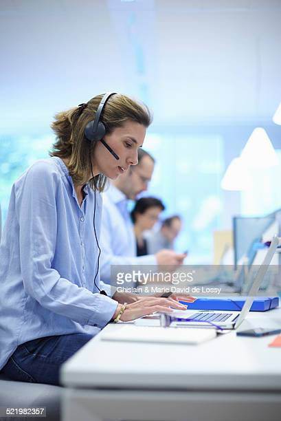 Business team using laptops in busy office