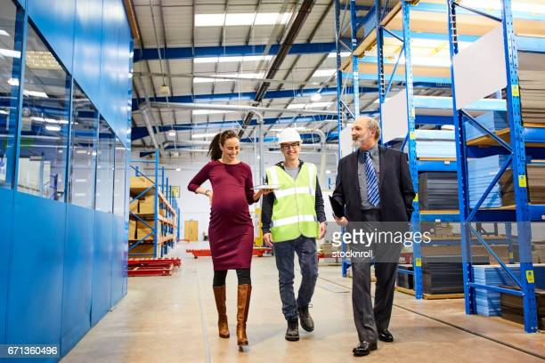 Business team walking in warehouse and discussing