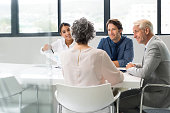 Positive multiethnic business people holding a meeting to sum up the results of the year. Group of happy business team during a meeting in a modern board room. Young businesswoman showing a business g