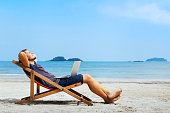 smiling businessman with computer relaxing on the beach