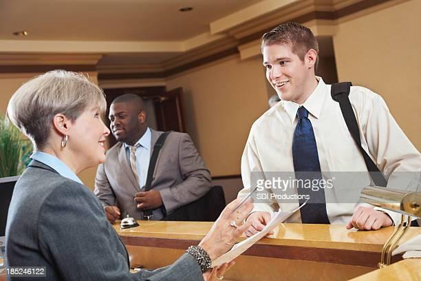 Geschäftsreisende, die Hotelrechnung mit den Mitarbeitern der Rezeption