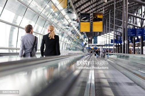 Business Travellers On Man Conveyor At Airport