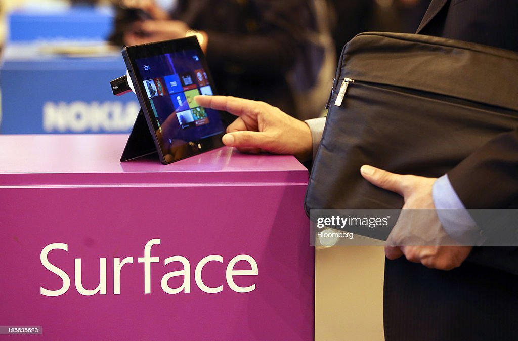 A business visitor uses a Windows Surface RT tablet, manufactured by Windows Corp., as it stands on display at the company's booth during the Apps World Multi-Platform Developer Show in London, U.K., on Wednesday, Oct. 23, 2013. Retail sales of Internet-connected wearable devices, including watches and eyeglasses, will reach $19 billion by 2018, compared with $1.4 billion this year, Juniper Research said in an Oct. 15 report. Photographer: Chris Ratcliffe/Bloomberg via Getty Images