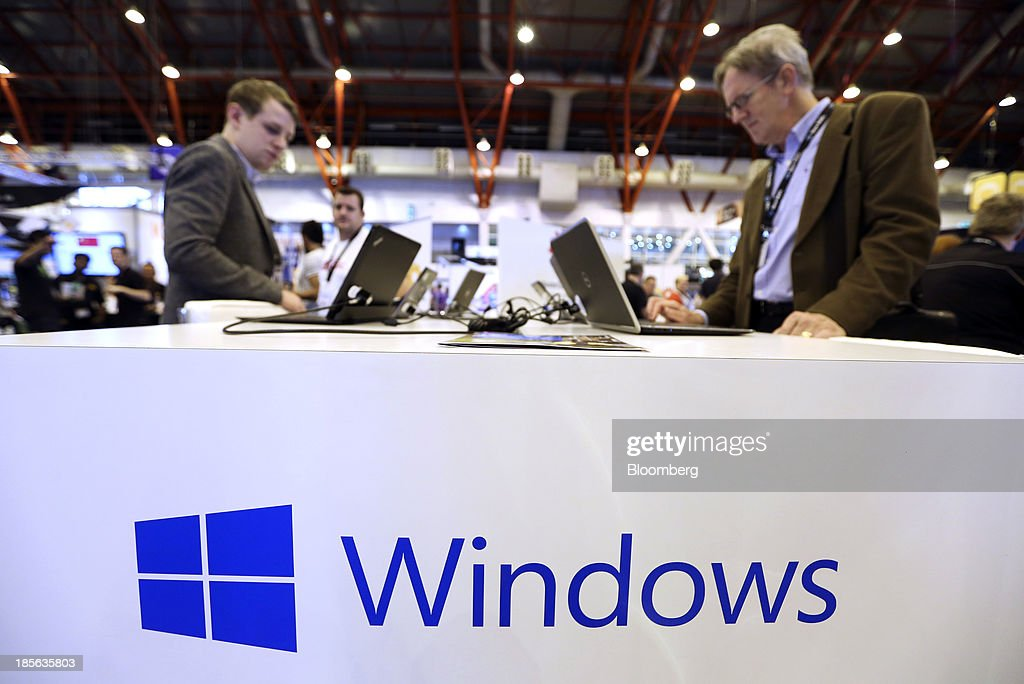 Business visitors use laptop computers on the Windows Corp. booth during the Apps World Multi-Platform Developer Show in London, U.K., on Wednesday, Oct. 23, 2013. Retail sales of Internet-connected wearable devices, including watches and eyeglasses, will reach $19 billion by 2018, compared with $1.4 billion this year, Juniper Research said in an Oct. 15 report. Photographer: Chris Ratcliffe/Bloomberg via Getty Images