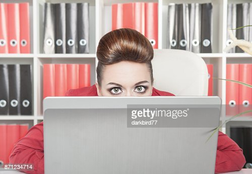 Business woman afraid and hiding behind the computer : Stock Photo