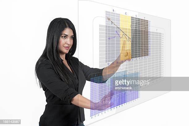 Business Woman Analyzing financial chart on transparent touchscreen