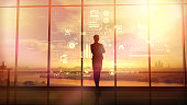 Silhouette of a woman in a huge office in front of large windows viewing corporate infographics.