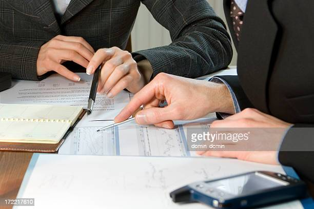Business woman and man with pens and papers