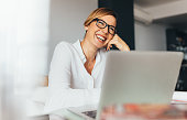 Smiling business woman in spectacles sitting at her desk in office. Woman sitting in office with laptop computer on her desk.