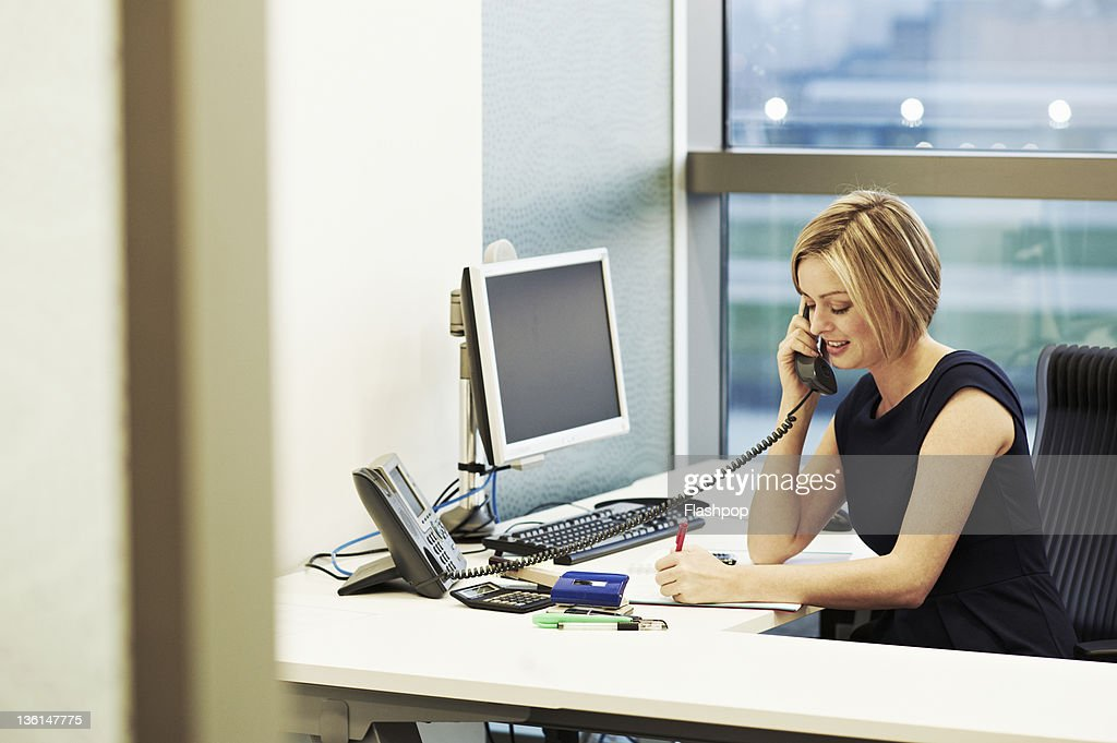 Business woman at her desk talking on telephone : Stock Photo