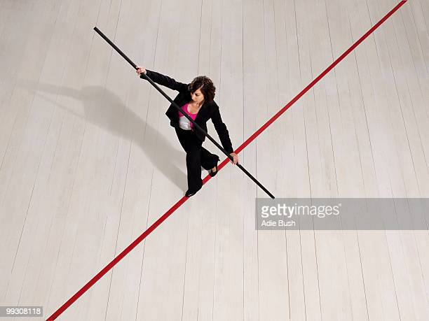 Business woman balancing on red line