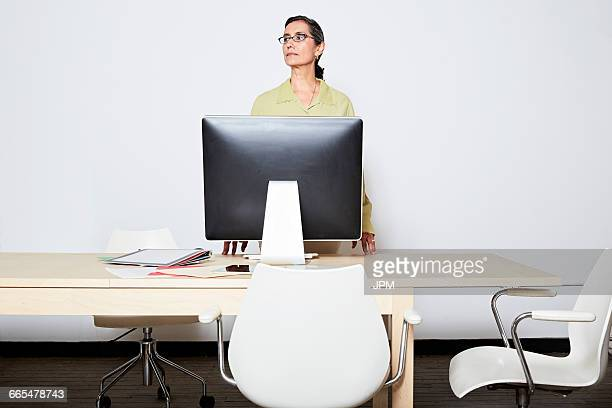 Business woman behind computer monitor looking away