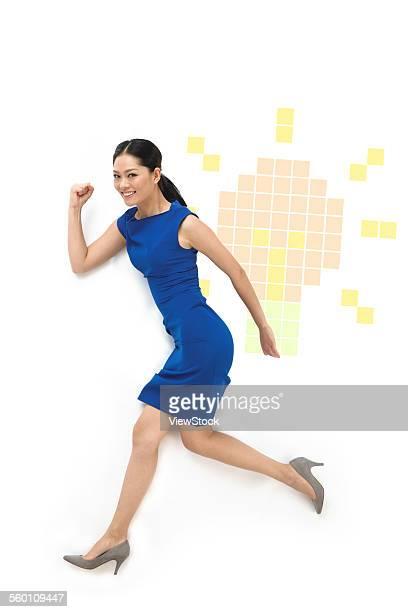 Business woman carrying a light bulb run