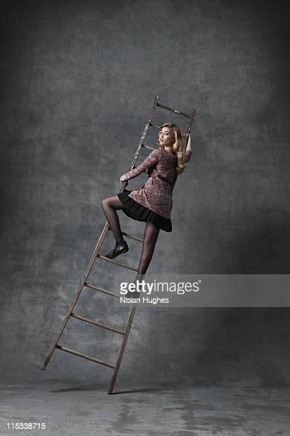 Business woman climbing on ladder