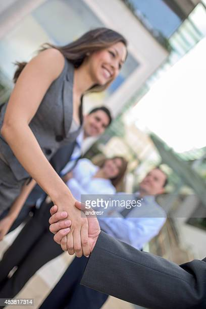 Business woman closing a deal with a handshake
