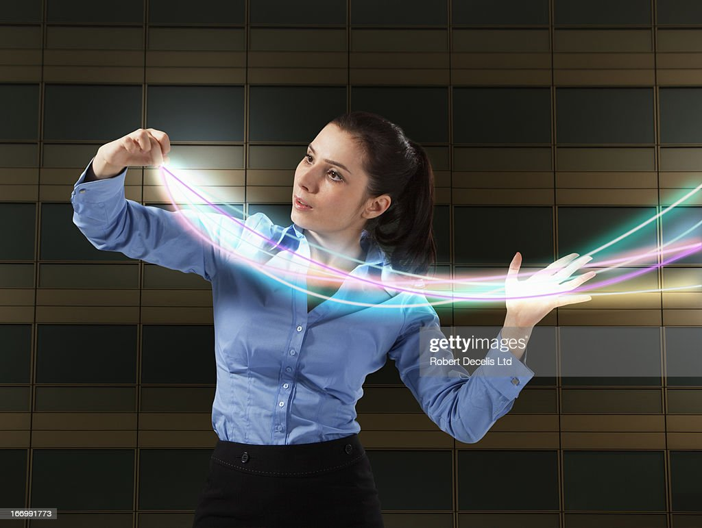 Business woman controlling light trails : Stock Photo