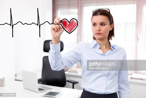Business woman drawing a heartbeat