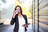 Business woman drinking coffee to go and hold tablet in the other hand in pause outside of office