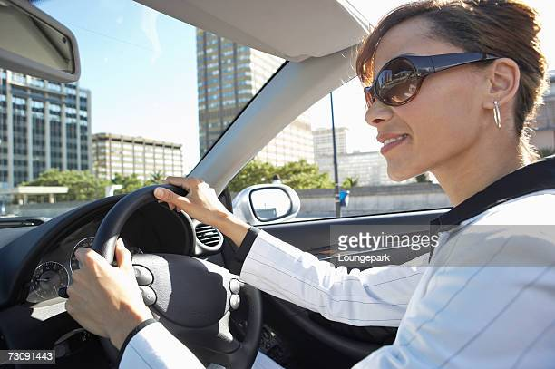 Business woman driving convertible car, close-up