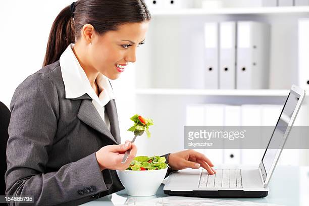 Business woman eating healthy vegetable salad.