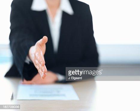 Business woman extending a handshake during an interview