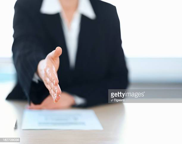 Business woman extending a handshake during an interview